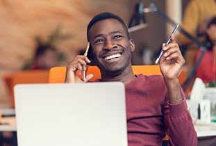 Happy young man on phone sitting behind laptop.